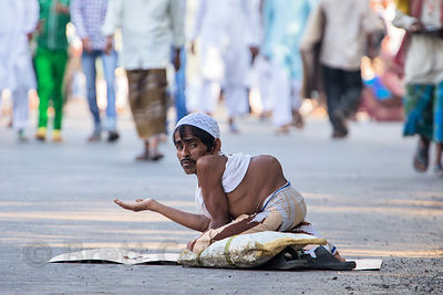 A muslim man with a spinal deformity begs during the Eid al-Adha, Red Road, Madian, Kolkata, India