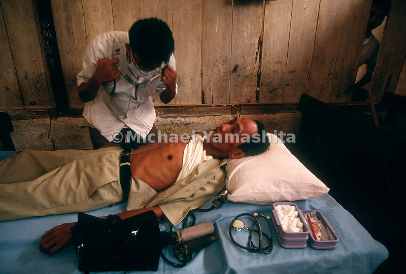 A doctor examines a patient after Indonesia's Plague of Fire.