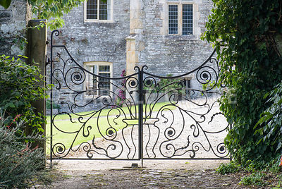Decorative wrought iron gates. The Cider House, Buckland Abbey, Yelverton, Devon, UK