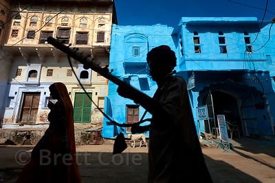 Musicians walk in front of a striking blue house in Pushkar, Rajasthan, India