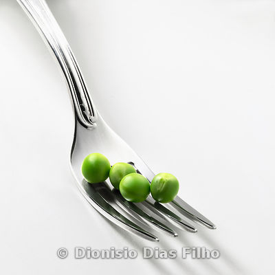 Fork with pea grains on white background