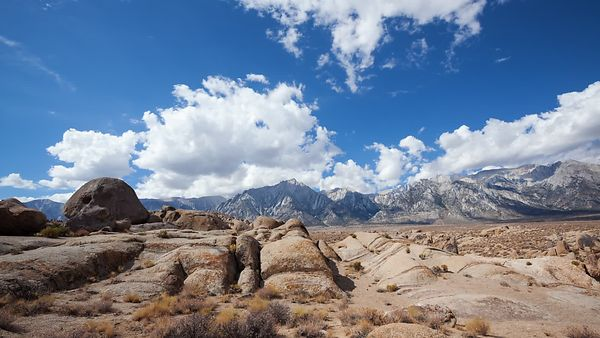 Wide Shot: Blue Skies, Fluffy White Clouds, & the Wind Swept Sandstone of the Alabama Hills Along the Majestic Sierras