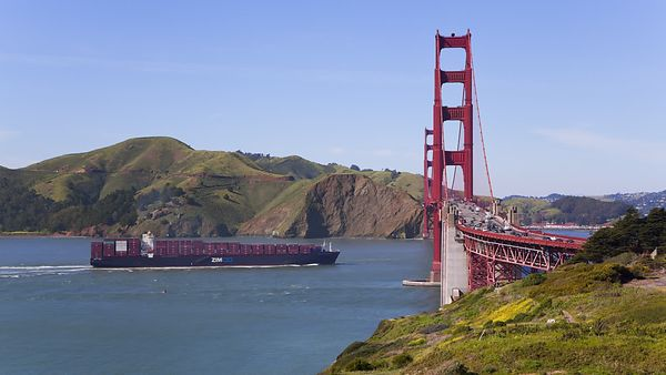Wide Shot: A Giant Barge Floats Under The Fast Traffic On The Golden Gate Bridge