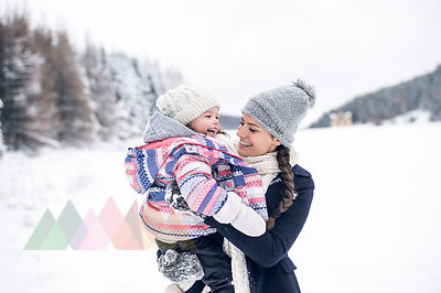 Happy mother carrying daughter in winter landscape