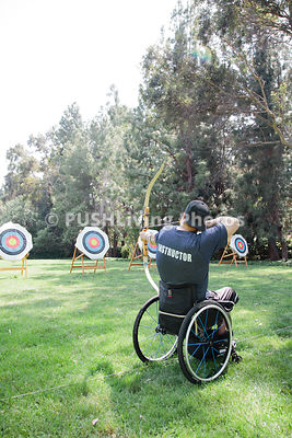Man in a wheelchair practicing archery