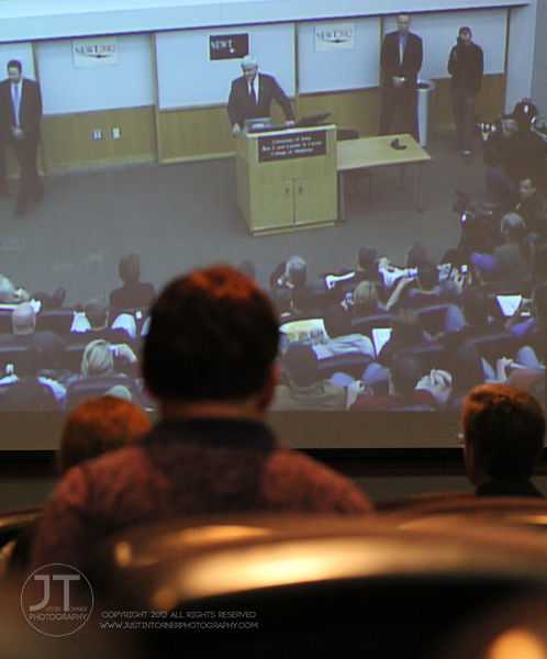 Onlookers watch a video feed of Newt Gingrich's speech in an overflow room adjacent to the room where he was speaking on the University of Iowa campus Wednesday in Iowa City.