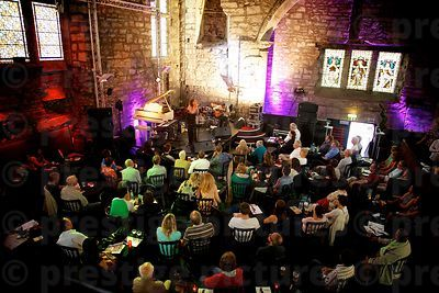 Old Stone Built Music Venue with Audience Watching a Singer on Stage
