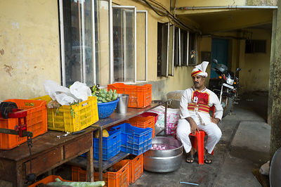 India - Thrissur - A waiter takes break outside the Indian Coffee House