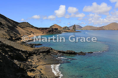 Bartolome Island, with a small submerged volcanic crater in foreground and Pinnacle Rock beyond, looking to Santiago, Galapagos Islands