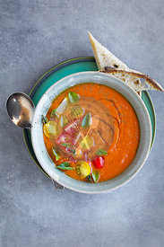 Roasted Tomato Herb Soup topped with cherry tomatoes and basil.