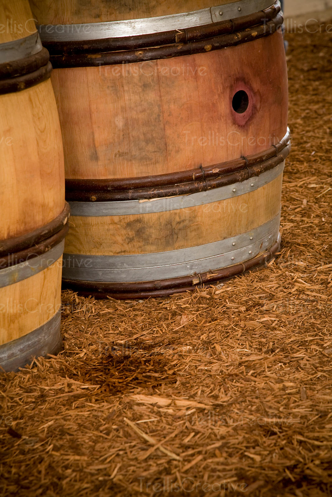 Two wine barrels sitting on a mulch floor