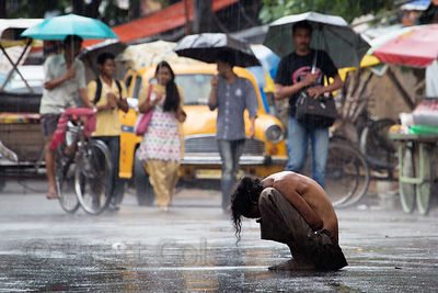 Mentally ill homeless man huddled on the street in pouring rain, Lake Gardens, Kolkata, India