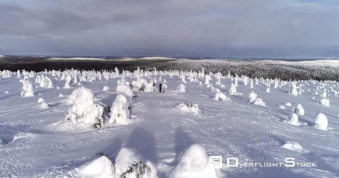 Photographer Hiking, Snowy Mountain, 4k Aerial View Over a Man Taking Pics on the Top of a Fjeld Tunturi, Full of Snow Covered Trees, Riisitunturi National Park, Lapland, Finland