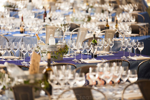 Many banquet tables set with wine glasses for a big party