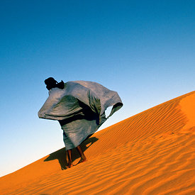 A man's robes flap in the wind as he climbs a dune overlooking Chinguetti