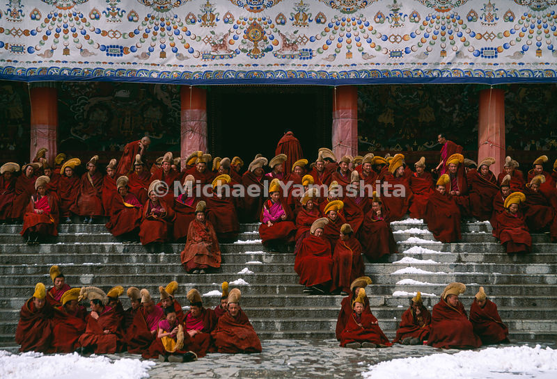 "In the chill of the early morning, monks gather on the steps of Labrang Monastery, awaiting prayers and their only meal of the day — sampa, made with yak butter tea. ""They have also immense Monasteries and Abbeys, some of them as big as a small town, with more than 2000 monks in a single abbey. These monks dress more decently than the rest of the people and have the head and beard shaven."" The Travels of Marco Polo, Vol 1, Book 1, Ch 61."