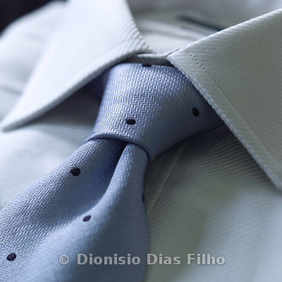 Detail of tie knot in a light blue shirt