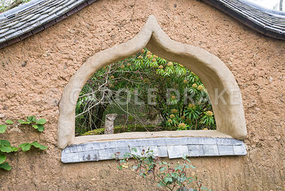 Ceramic figure by Carole Blackwel seen through 'window' in cob wall of the Pond Garden. Caervallack Farm, St Martin, Helston, Cornwall, UK