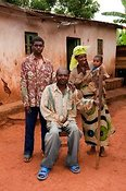 Rwandan family out side home. Father is disabled and uses a crutch. Rwanda