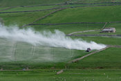 Contractor spreading lime on pastures to improve soil quality, in Wensleydale, North Yorkshire, UK.