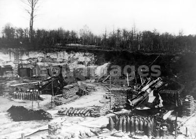 WWI artillery position showing guns, ammunition shells, sandbags, and lean-tos
