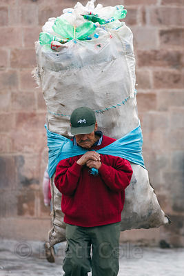 A man carries an enormous load of plastic bottles that he's collecting to recycle, Cusco, Peru