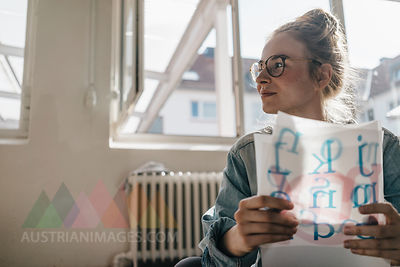 Young woman holding letter templates looking sideways