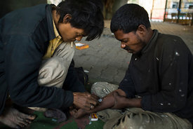 India - New Delhi - Homeless addicts prepare and inject heroin under a flyover