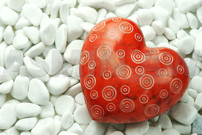 Red heart on white stones