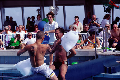 Passengers watch a pillowfight over the swimming pool on the deck of the P&O liner Oriana
