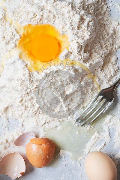 A raw egg in flour beside eggshells and a fork.
