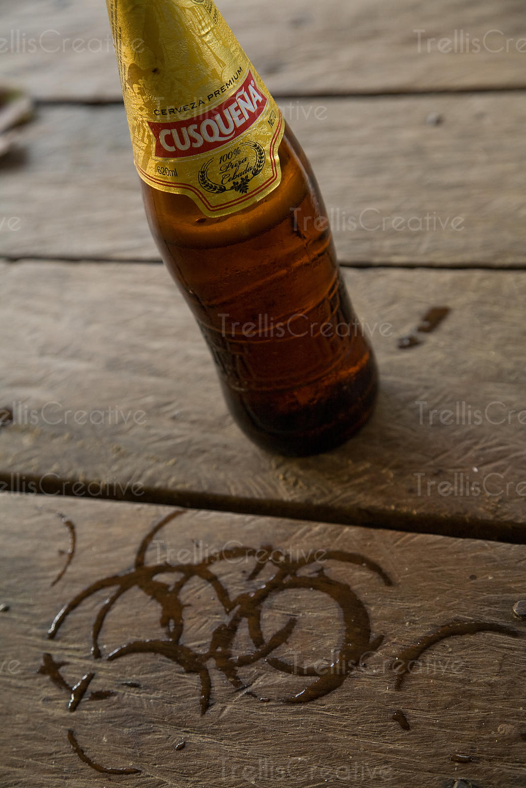 A frosty beer leaves wet rings on a wooden patio