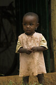African baby girl with earings standing outside doorway to traditional hut Kenya Africa