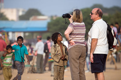 A boy asks foreign tourists for money at the Pushkar Camel Fair, Pushkar, Rajasthan, India