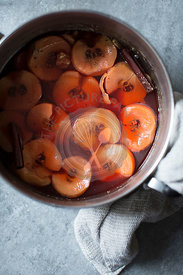 Poached Quince Fruit, simmering in a pan.