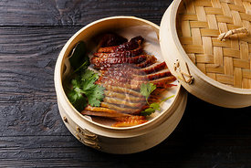 Sliced Peking Duck in bamboo steamer with fresh cilantro on black burned wooden background