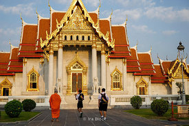 A monk and students at Wat Benchamabophit, a Buddhist temple in the Dusit district of Bangkok, Thailand. Also known as the marble temple.