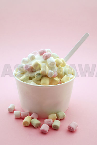 Fresh frozen yoghurt with small marshmallows in a paper cup on a pink background