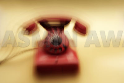 Old red telephone on gold background with scratches and marks Long exposure with lens zoom effects Studio shot