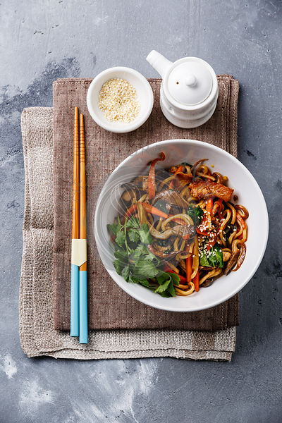 Udon stir fry noodles with Chicken meat and vegetable in bowl on concrete background