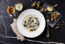 Risotto with morels on plate and Dried morels on dark marble table background