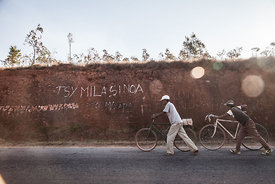 "Men walk past graffiti reading ""We don't need Chinese"" in Soamahamanina (70 kilometer from Antananarivo) on September 29, 2016 in protest against the presence of the Chinese mining company Jiuxing. Protestors in Soamahamanina demonstrated on September 29 in protest against the presence of the Chinese mining company Jiuxing. The protesters, native to the region, accuse Chinese mining company Jiuxing of forcing the rental of land and destroying the property and environment."
