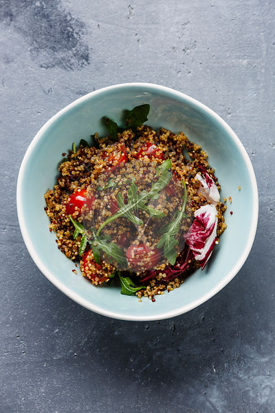 Salad with quinoa, tomato and arugula in bowl on concrete background