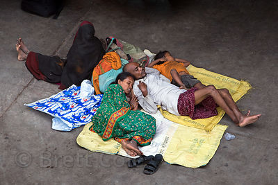 A homeless family sleeps on concrete, using each other for pillows, in the Paharganj area of Delhi, India