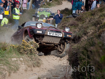 a Triumph TR7 is airborn at the start of the last steep hill on the Blue Hills section of the MCC Land's End Trials