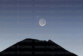 One day old new moon and Jupiter setting into Parinacota volcano crater shortly after sunset, Sajama National Park, Bolivia