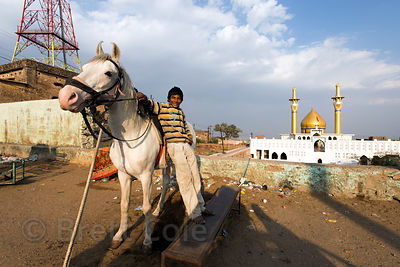 A boy and his horse at the beautiful mosque near Taragarh fort, Ajmer, Rajasthan, India. He charges tourists to sit on the horse for a photo-op with the Mosque in the background.