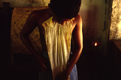 India - Kerala - A boy adjusts his loin cloth before a massage by his teacher