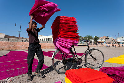 A boy transports brightly colored dyed fabrics in a courtyard in Jodhpur, Rajasthan, India