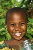 Young girl smiling at camera holding glass of milk Uganda Africa